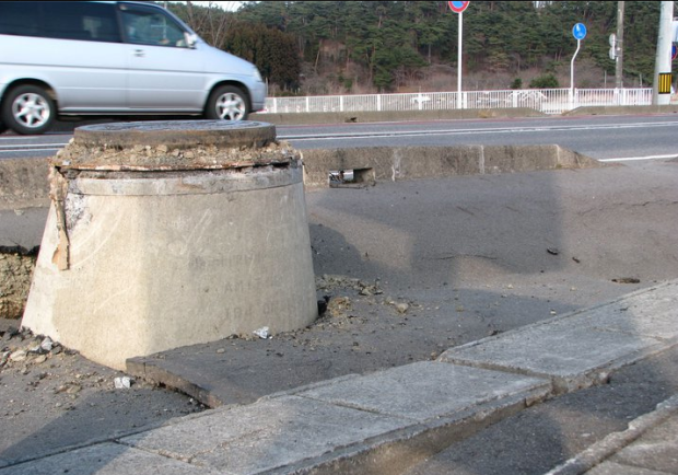 Manhole and pipe that were forced out of the ground.